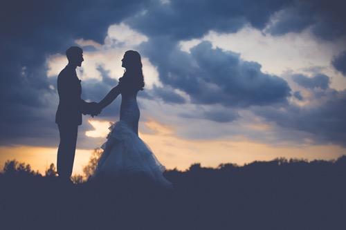 ウェディングドレスを着て手をつなぐカップル