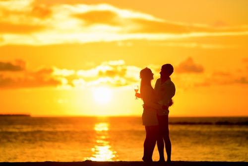 カップルが愛し合い、浜辺でハグしている
