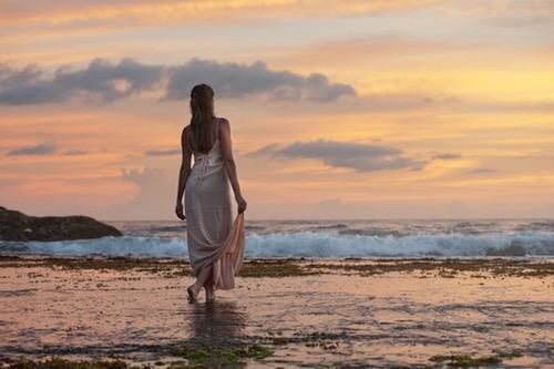 清楚な感じの女性が浜辺を歩いている
