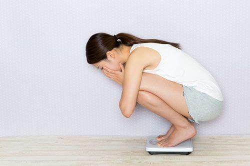 体重計を見て驚く女性