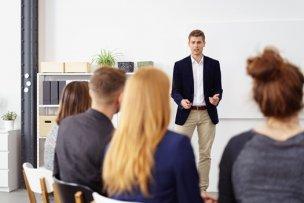 ビジネスカジュアルで講演をする男性とリスナー