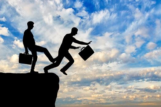 崖から落とされようとしているビジネスマン