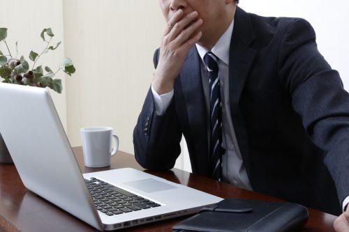 パソコンの画面を見て考える男性