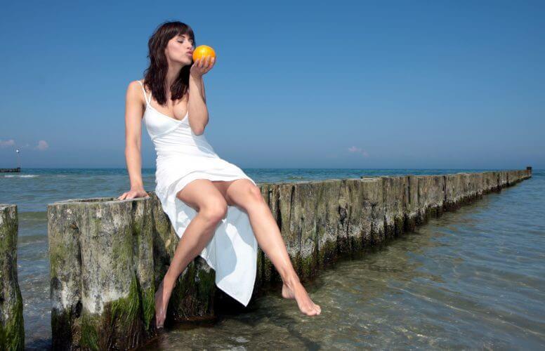 グレープフルーツをかじる女性